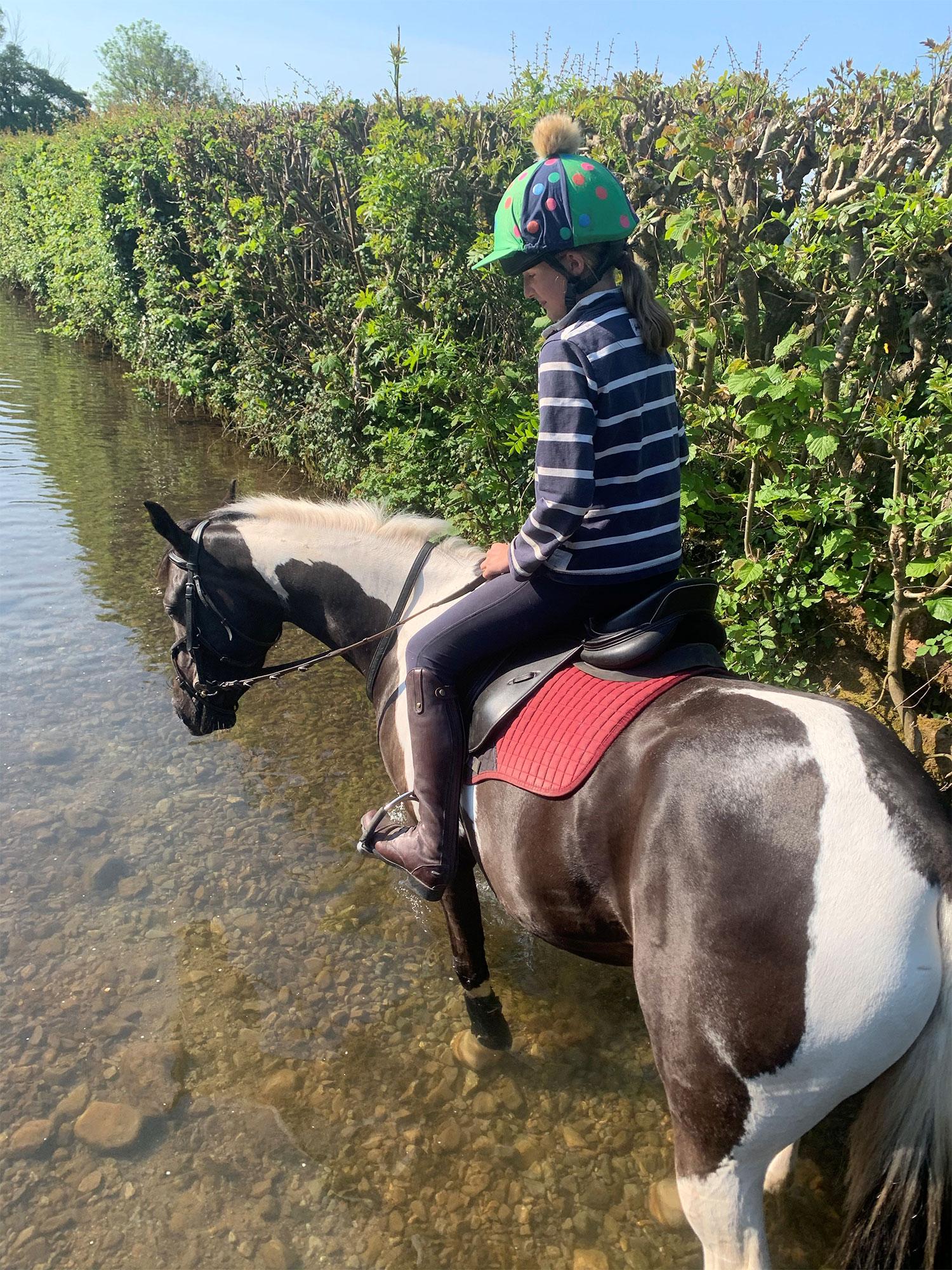 Horse and girl walking through a stream